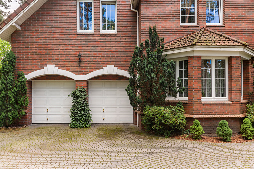 Red brick classic style house with white garage doors and window frames. Cobble in front of the building.
