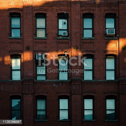 Red brick facade with blue windows and sun rays in New York