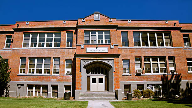 Red Brick High School Building Exterior Exterior of large brick high school on a sunny day. high school building stock pictures, royalty-free photos & images