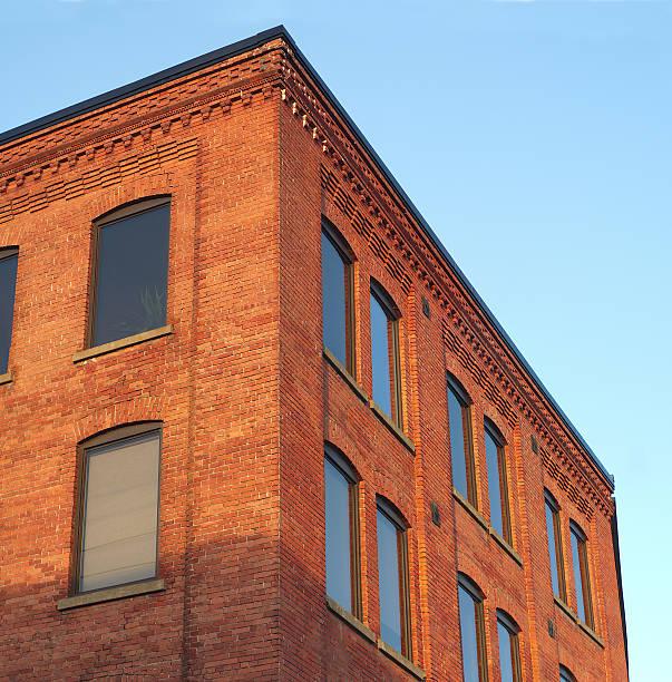 red brick office building corner in sunlight blue sky - altbau stock-fotos und bilder