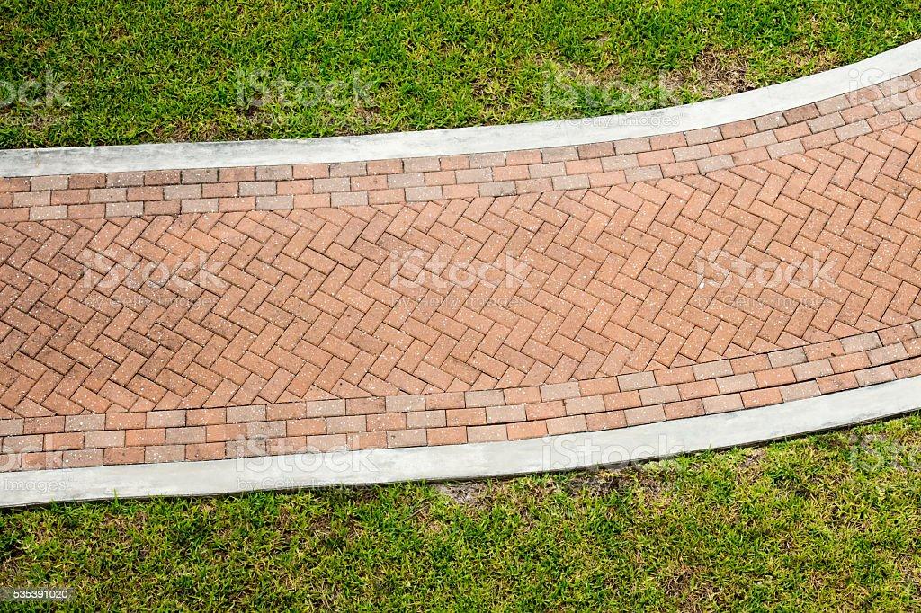 Red brick pattern sidewalk through grass stock photo