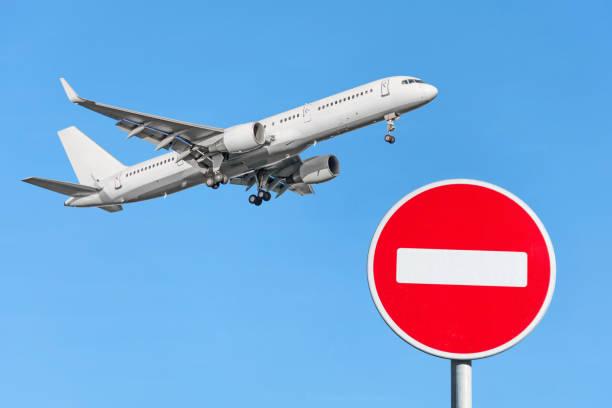 붉은 벽돌 정지 표지판 및 하늘에 비행 비행기. 비행 금지 개념 - 금지됨 뉴스 사진 이미지