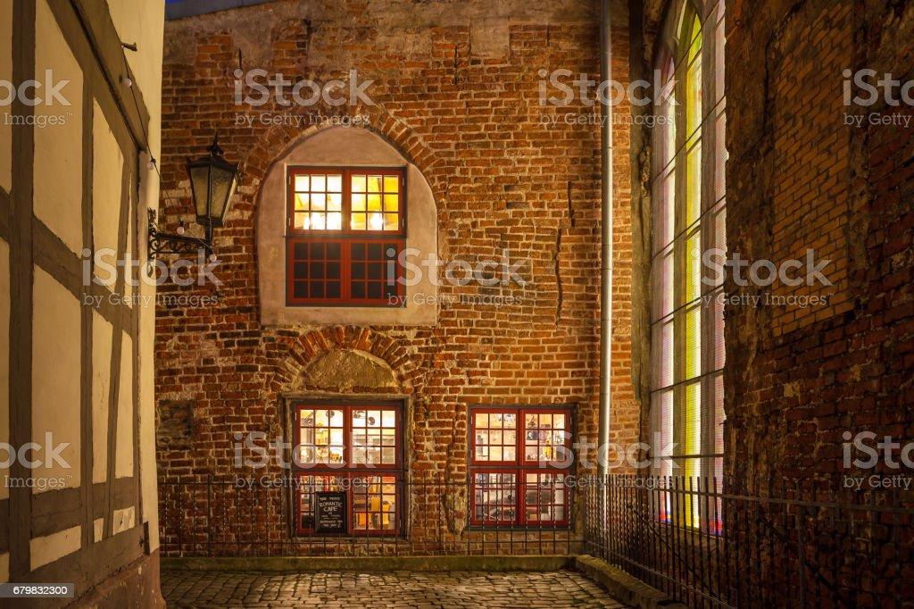 RIGA, LETTONIE - 25 DÉCEMBRE 2015. Mur de briques rouges de la vieille maison à Riga, de façon à café plus romantique dans la vieille ville. Scène de nuit, éclairée de fenêtres. - Photo