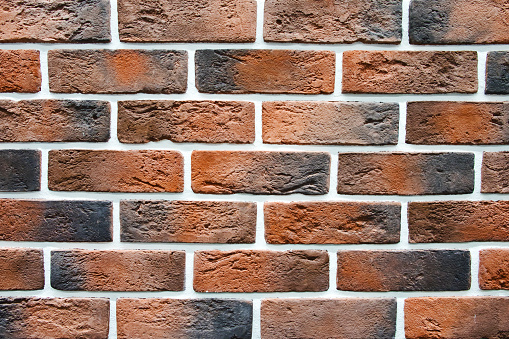 Background red wall bricks with cement closeup. Red brick wall texture decoration panel.
