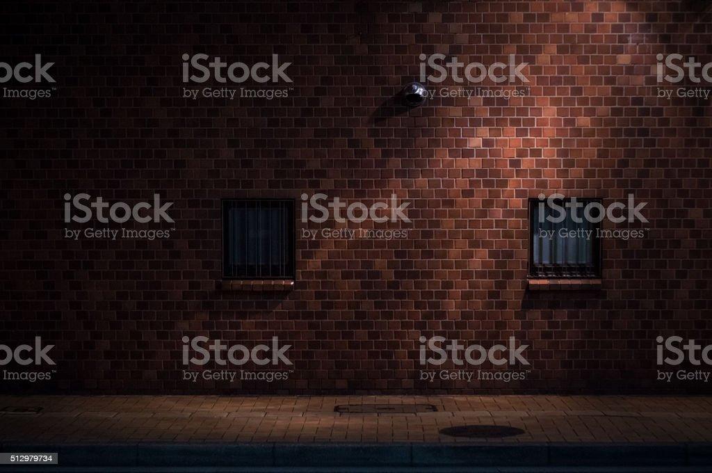 Red brick wall under street light in midnight stock photo