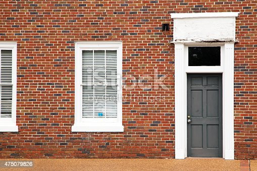 istock Red brick wall with door and windows 475079826