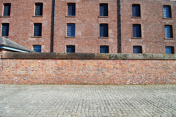 Red brick wall with sidewalk at the Albert Dock, Liverpool stock photo