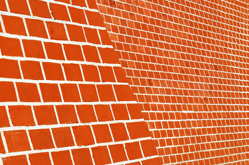 Red brick wall with white seams. Side view.
