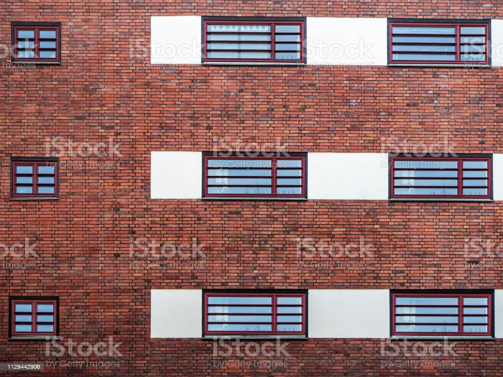 Red brick wall with windows in Berlin, Germany. Brick facade.