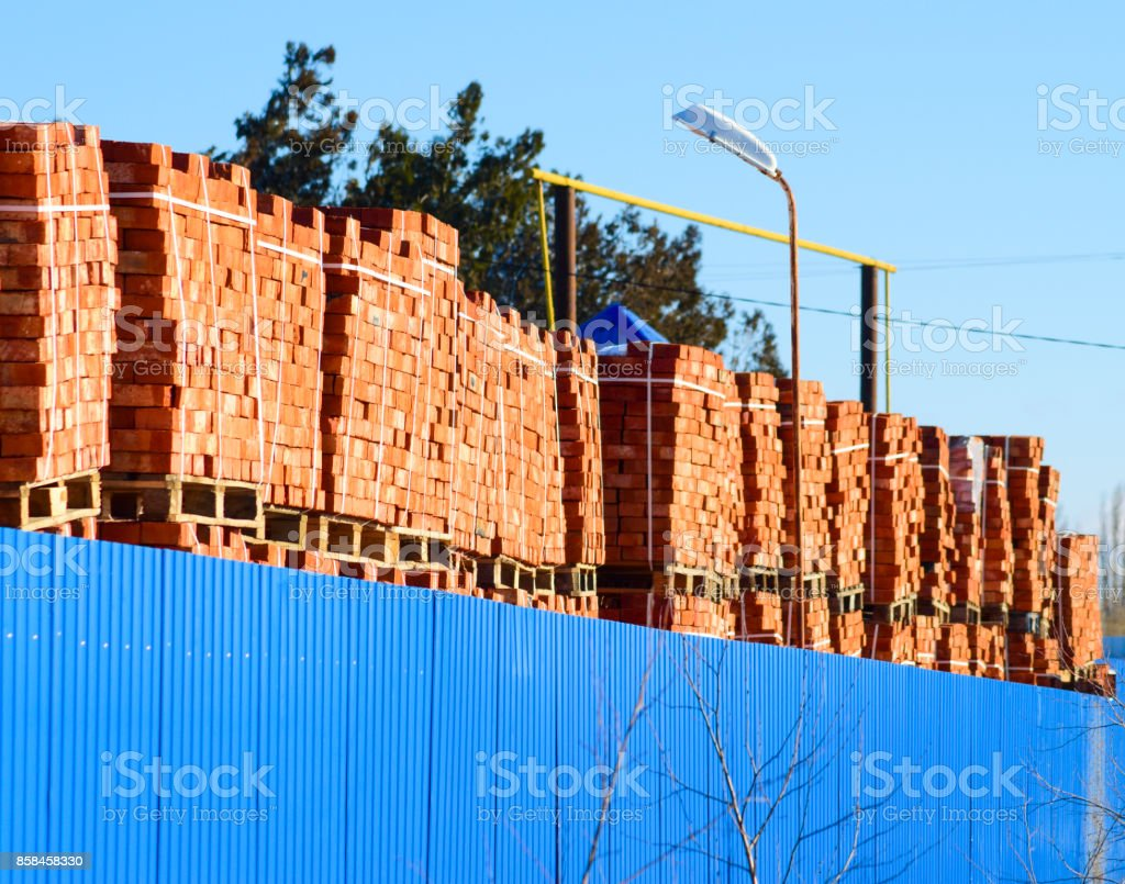 Red bricks stacked into cubes. Warehouse bricks. Storage brickworks products stock photo