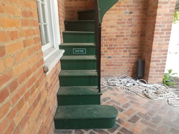 red bricks with green stairs and sign that says staff only stock photo