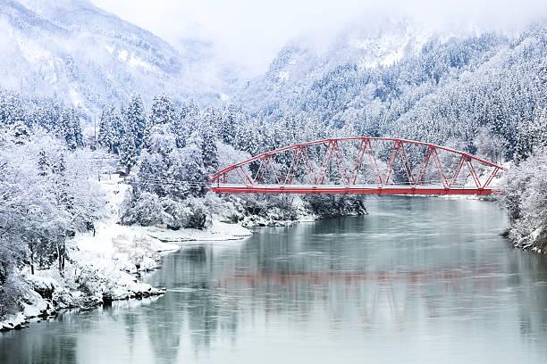 rote brücke winter-landschaft - weihnachten japan stock-fotos und bilder