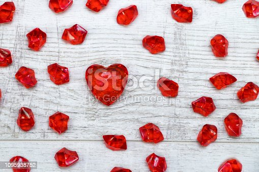 Red brilliant hearts on wooden background