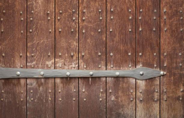 Rotbraune Holztür mit Nieten – Foto