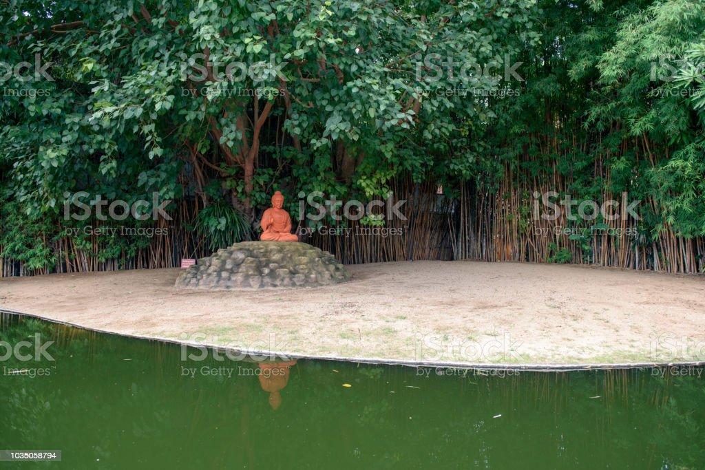 Red Buddha statue siting under Bodhi tree stock photo