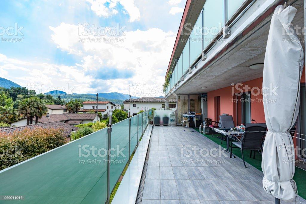 Edificio Rojo Exterior Con Gran Terraza Y Vidrio Parapeto