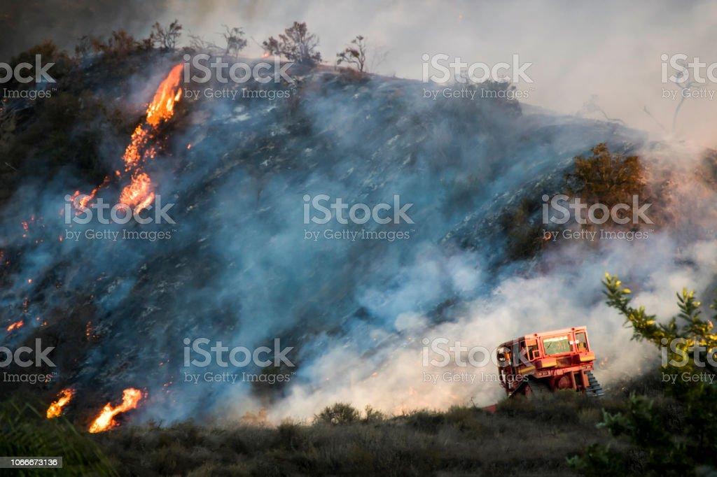 Red Bulldozer with Burning Hillside during California Woolsey Brushfire stock photo