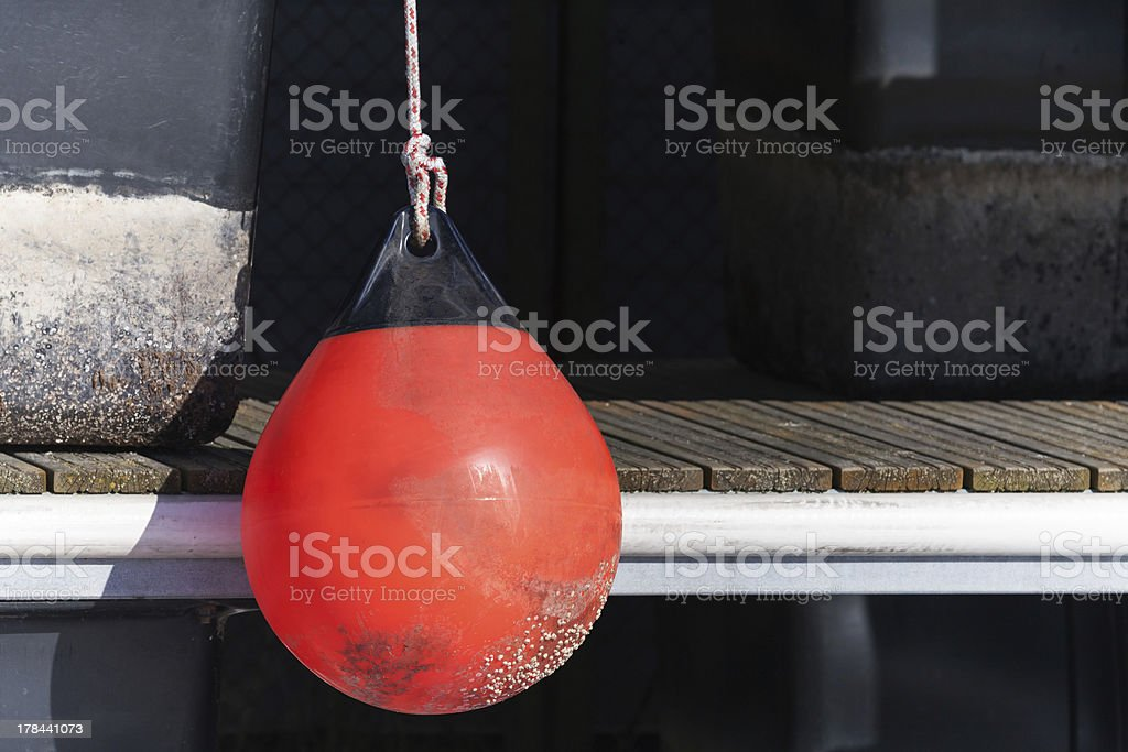 Red buoy for protecting moored yachts in marina stock photo