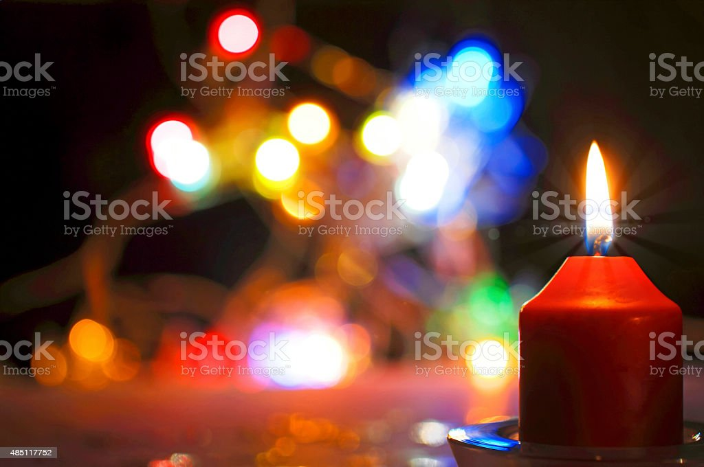 red burning candle and colorful lights stock photo