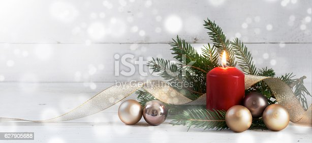 istock Red burning candle with christmas decoration on white wood 627905688