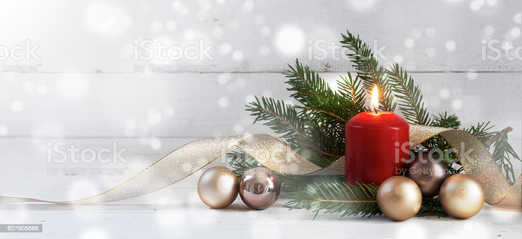 Red burning candle with christmas decoration on white wood stock photo