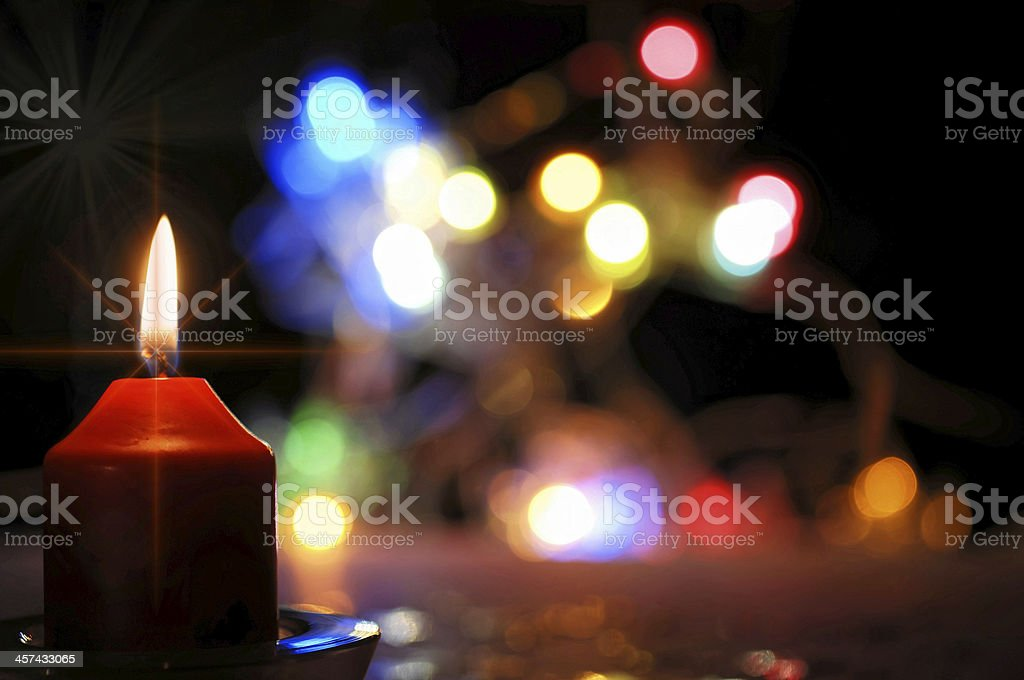 red burning candle with colorful lights stock photo