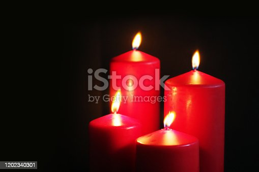 Red burning candles on a black background