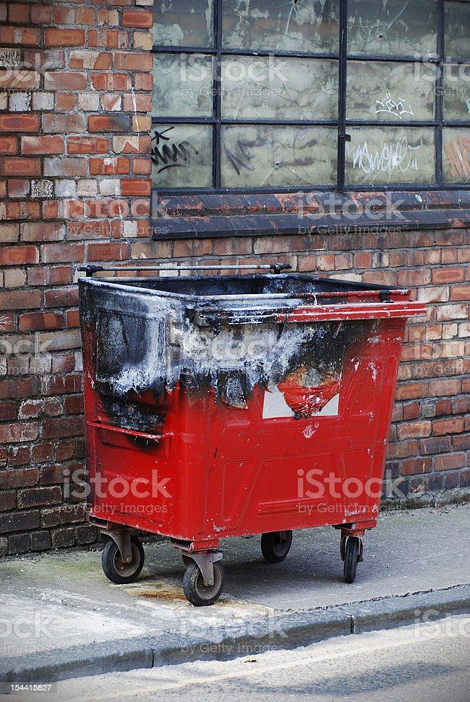 Red burnt trash bin in the street stock photo