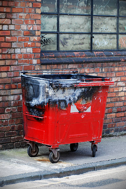 Red burnt trash bin in the street Red burnt trash bin in the street dumpster fire stock pictures, royalty-free photos & images