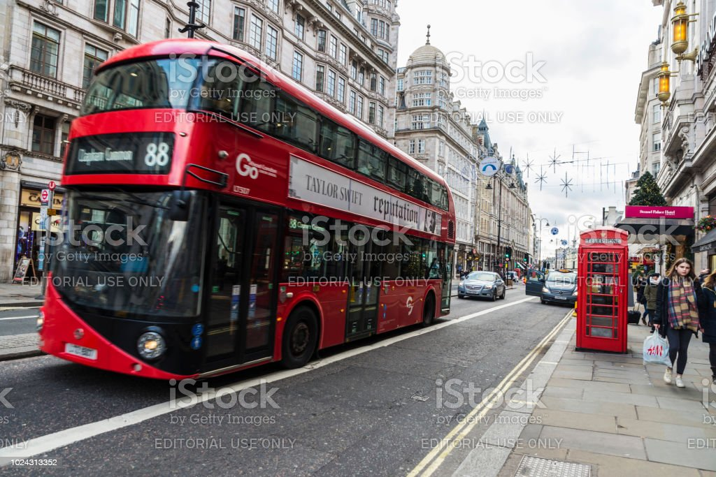 Red bus circulating in London, United Kingdom London, United Kingdom - January 1, 2018: Red double-deckers bus circulating with people around and a telephone box in London, United Kingdom Advertisement Stock Photo