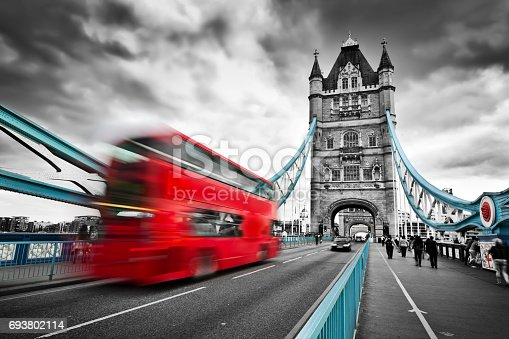 Red bus in motion on Tower Bridge in London, the UK. Dramatic rainy clouds. Black and white with red and blue bridge elements.