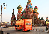 Moscow, Russia - April 31, 2019: Red sightseeing bus on the background of St. Basil's Cathedral.
