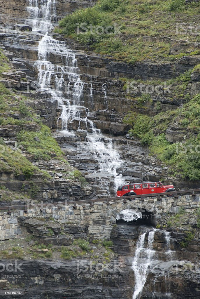 Red Bus passing a waterfall in Glacier National Park Montana royalty-free stock photo
