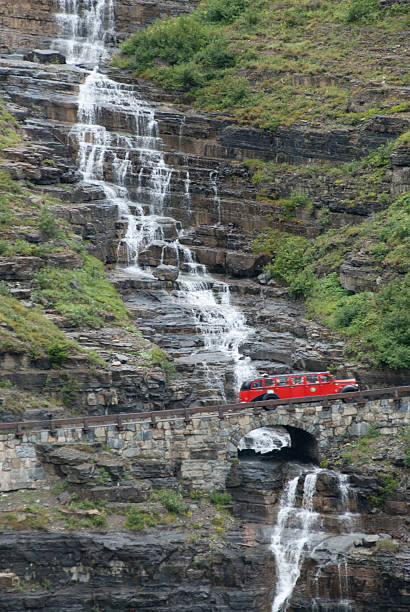 Red Bus passing a waterfall in Glacier National Park Montana stock photo