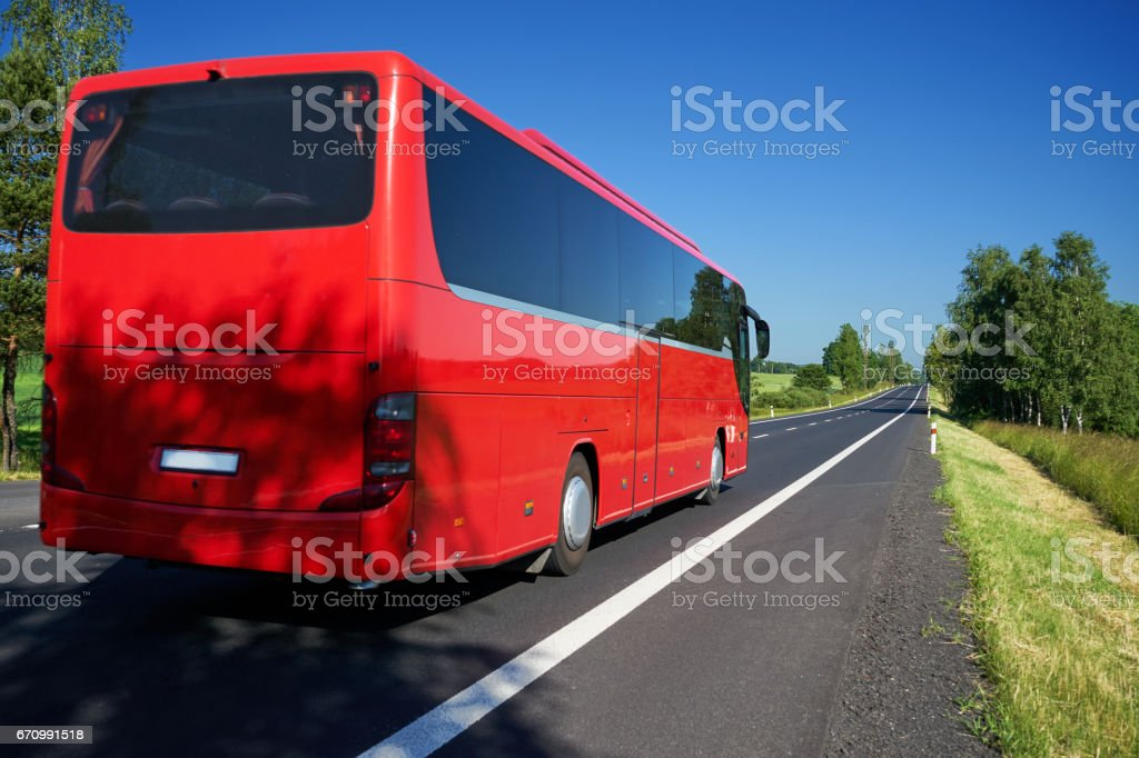 Red bus traveling on asphalt road lined avenue of trees stock photo