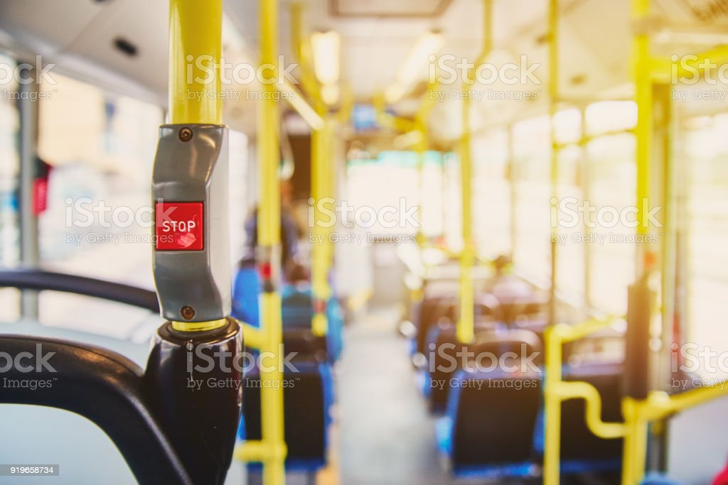 Red button STOP on the bus. Bus with yellow handrails and blue seats. Photo with the sun effect, glare on the lens from the light. Spacious interior of the bus, bright button with focus. stock photo