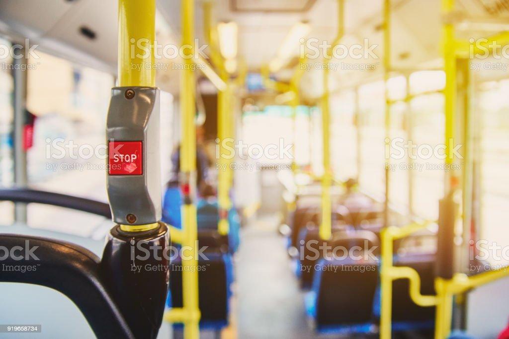 Botón rojo de parada en el autobús. Bus con asientos azul y amarillo pasamanos. Foto con el efecto del sol, brillos en el lente de la luz. Espacio interior del autobús, botón brillante con enfoque. - foto de stock