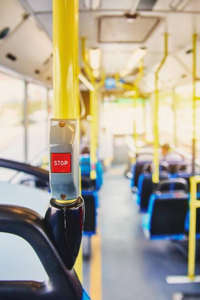 """rote taste stop auf den bus. bus mit gelben handläufen und blauen sitze. foto mit dem sonne-effekt, die blendung auf dem objektiv aus dem licht. geräumigen innenraum des busses, schaltfläche """"hell"""" mit schwerpunkt. - abschiedswünsche stock-fotos und bilder"""