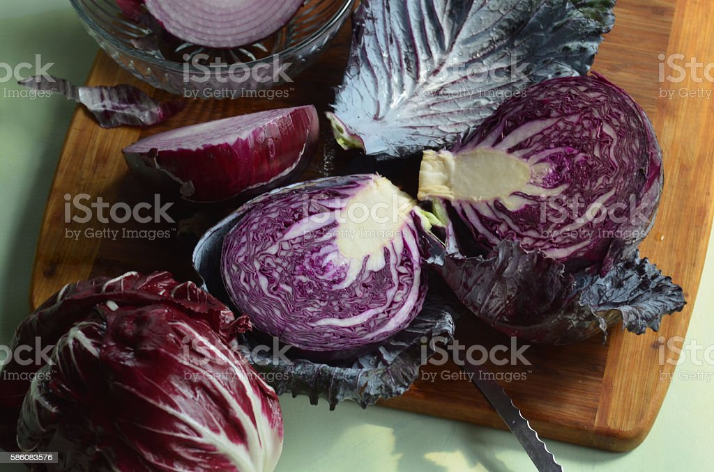 red cabbage halves on cutting board, red onion, radicchio stock photo