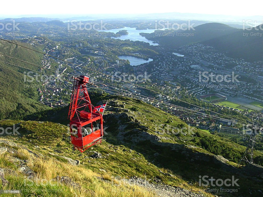 Red cable car traveling above landscape view of Bergen stock photo
