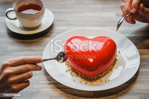 Red cake in the shape of a heart is on the table. Two hands with spoons, male and female, stretch into a pie. Romantic date, Valentine's Day.