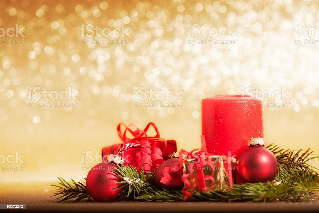 red candle decorated for Christmas with baubles and gifts stock photo
