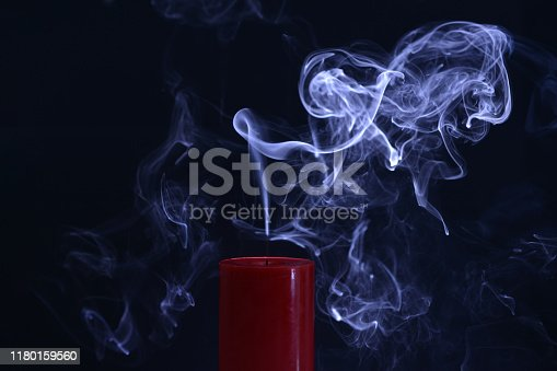 Red Candle with white smoke on black background