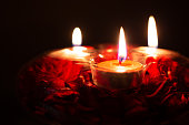 red candles in a candlestick on a black background, close-up