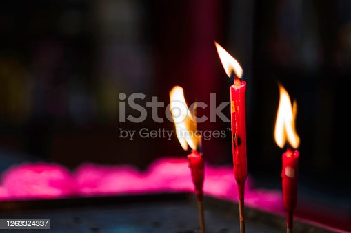 3 red candles for prayers in a temple located in Petaling Street, Malaysia