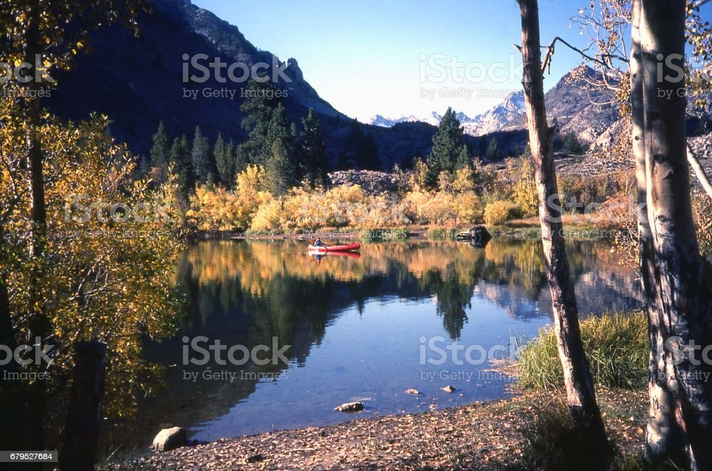 Red canoe in mountain lake and reflection of Sierra Nevada Mountains in autumn near Bishop California royalty-free stock photo
