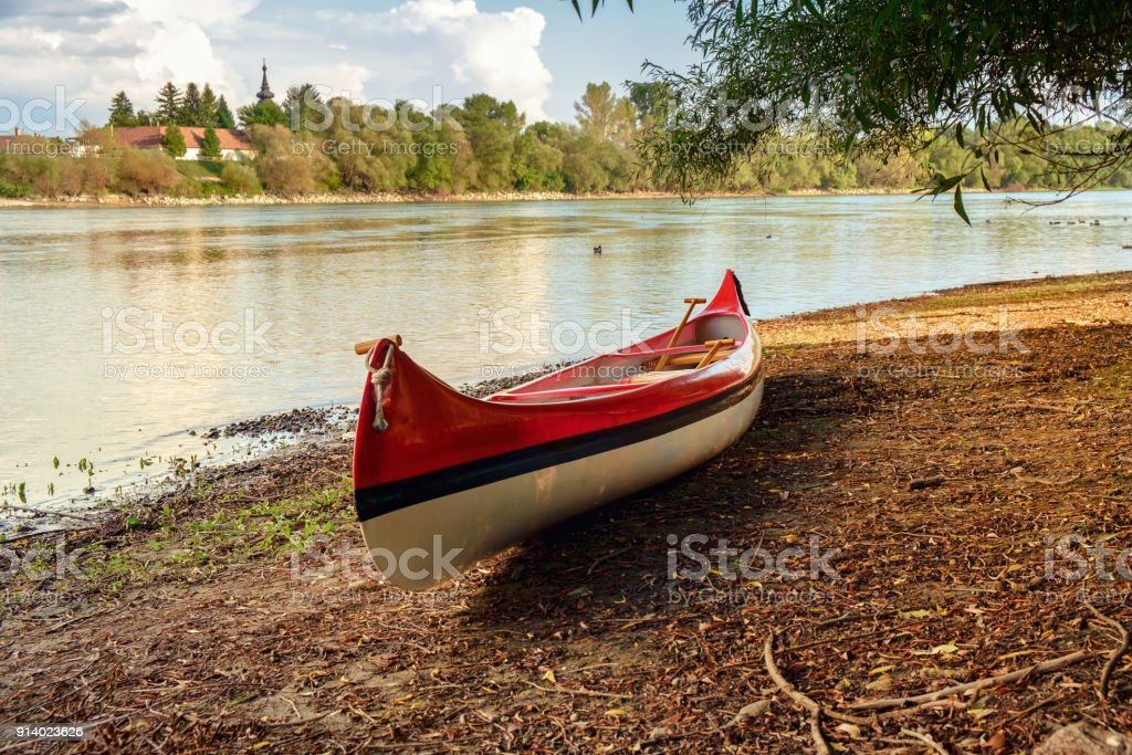 Red canoe on beach at river Danube stock photo