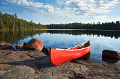 istock Red canoe on rocky shore of calm northern lake 545361556