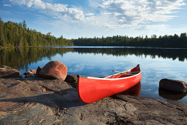 red canoe on rocky shore of calm northern lake - vattenbryn bildbanksfoton och bilder