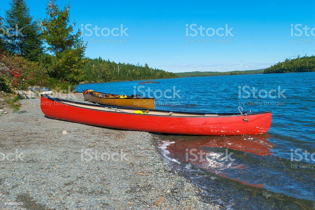 Red canoe on rocky shore  of Moose Lake BWCA stock photo